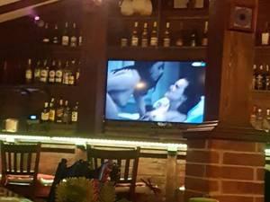 Pe ecranul televizorului situat deasupra barului au rulat scene porno, dintr-un film pentru adulţi